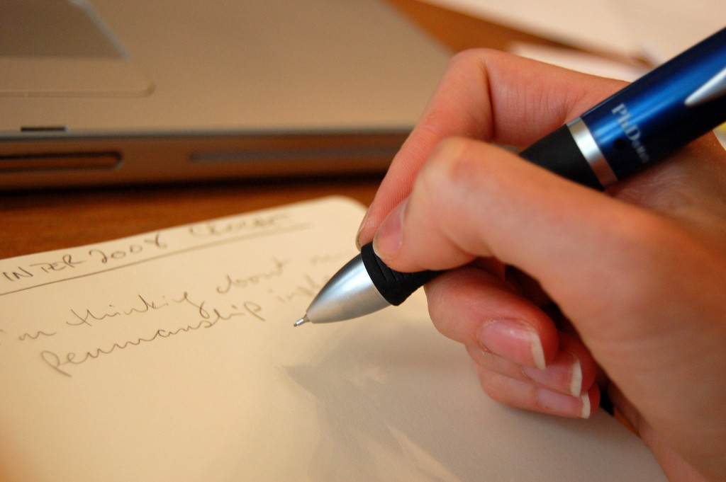 woman's hand writing with pen