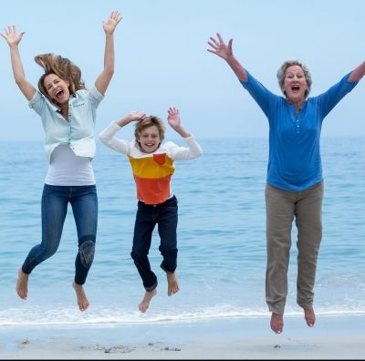 Joyful family jumping in air at beach